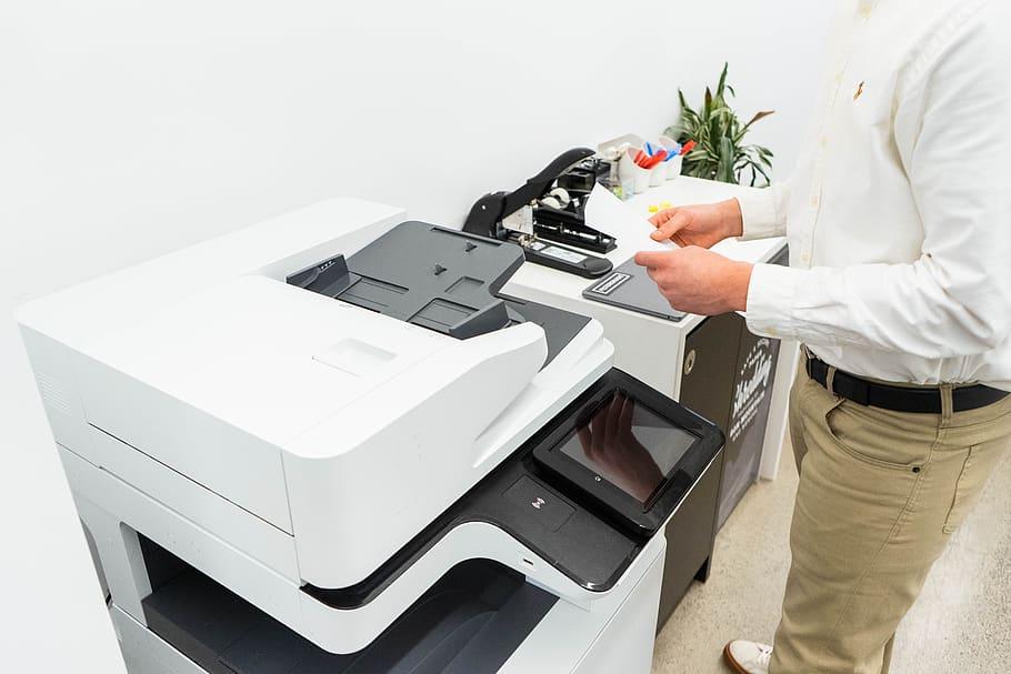 seseorang mencoba cara mengatasi paper jam pada mesin fotocopy canon
